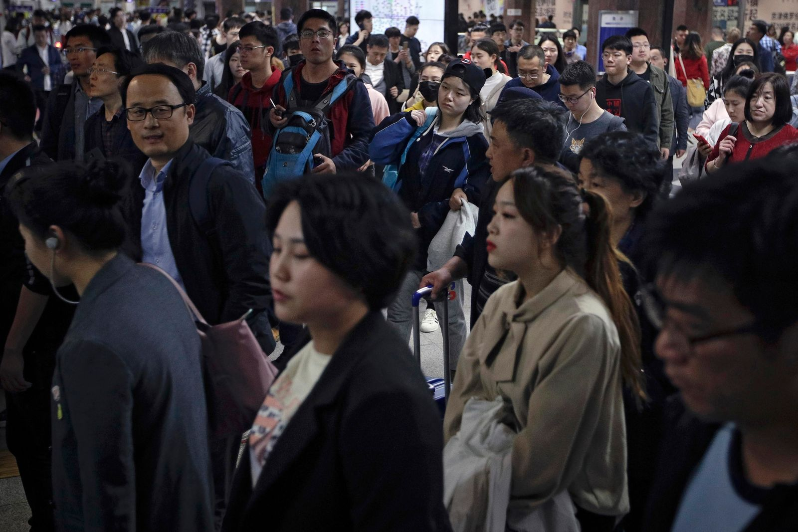 In this Wednesday, April 17, 2019, photo, Chinese people rush to catch their trains at a subway station during the evening rush hour in Beijing. Remarks by the head of Chinese online business giant Alibaba, Ma Jack, one of China's richest men, that young people should work 12-hour days, six days a week if they want financial success have prompted a public debate over work-life balance in the country. (AP Photo/Andy Wong)