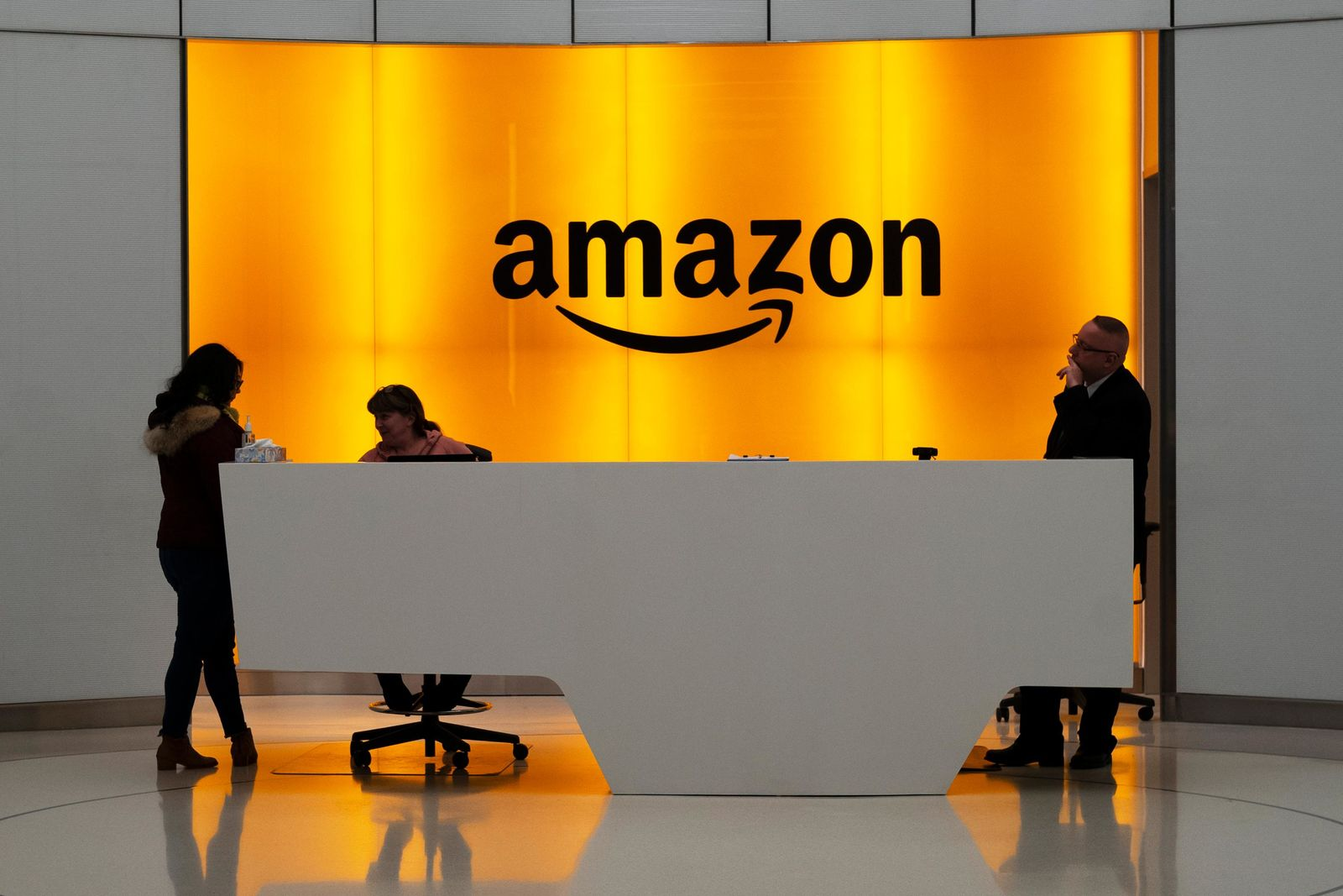 FILE - In this Feb. 14, 2019 file photo, people stand in the lobby for Amazon offices in New York. (AP Photo/Mark Lennihan, File)