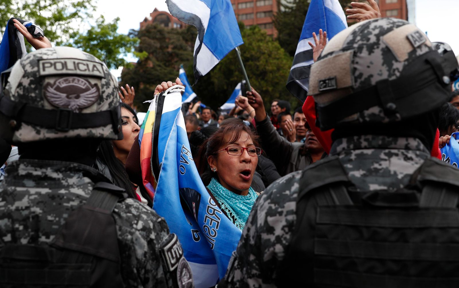 Police stand guard as supporters of Bolivian President Evo Morales, who is running for a fourth term, rally outside the Supreme Electoral Court where election ballots are being counted in La Paz, Bolivia, Monday, Oct. 21, 2019. (AP Photo/Juan Karita)