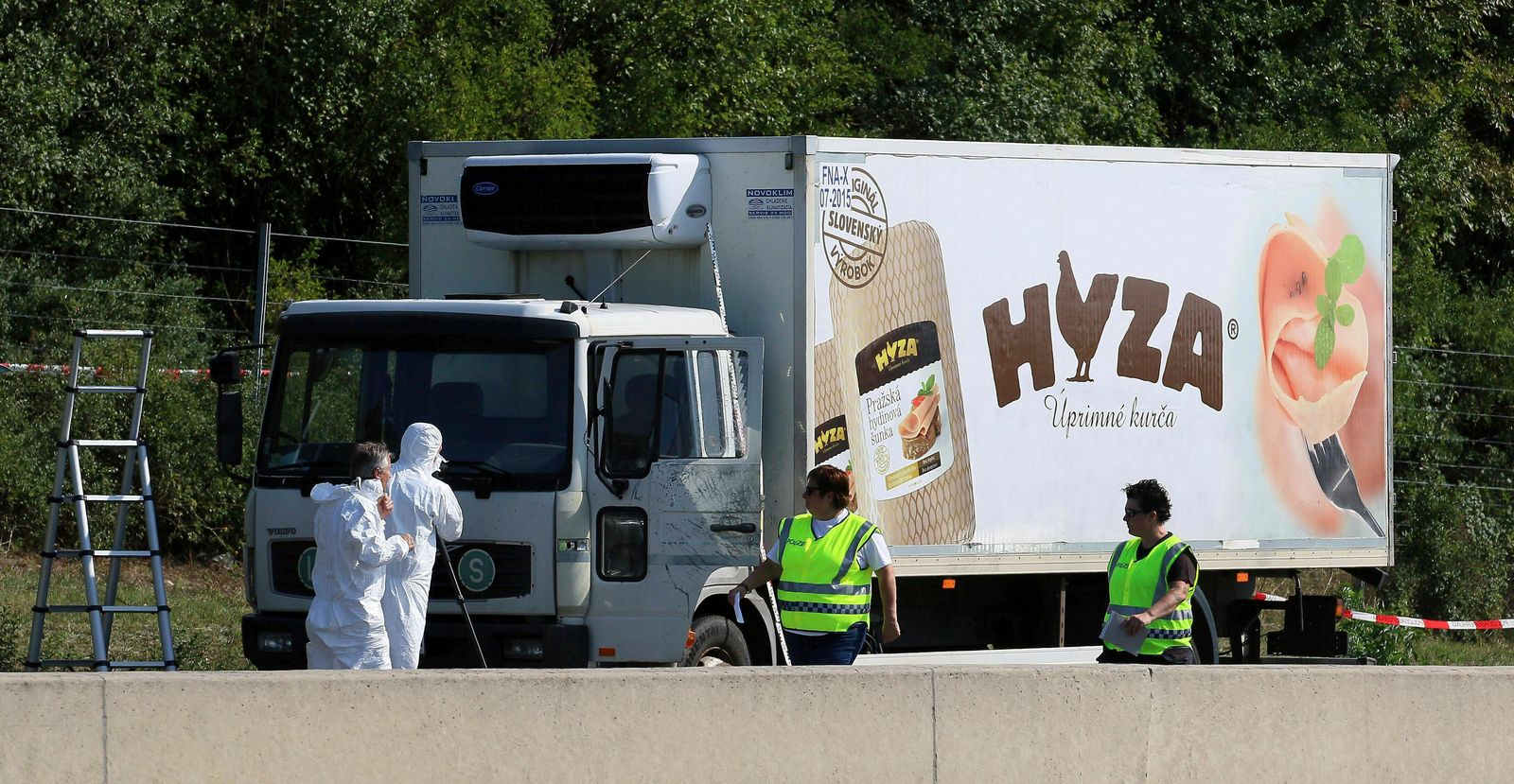FILE - In this Thursday, Aug. 27, 2015 file photo, investigators stand near an abandoned truck on the shoulder of Highway A4 near Parndorf, Austria, south of Vienna.{ } (AP Photo/Ronald Zak, file)