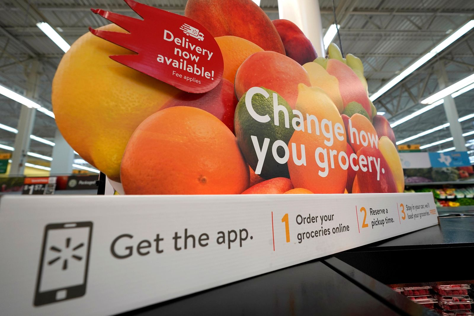 In this Nov. 9, 2018, file photo a sign promotes online and home delivery of groceries at a Walmart Supercenter  in Houston. Retailers are taking back some control of the store experience with smart phone app features that let customers do things like scan and pay and download digital maps. (AP Photo/David J. Phillip, File)