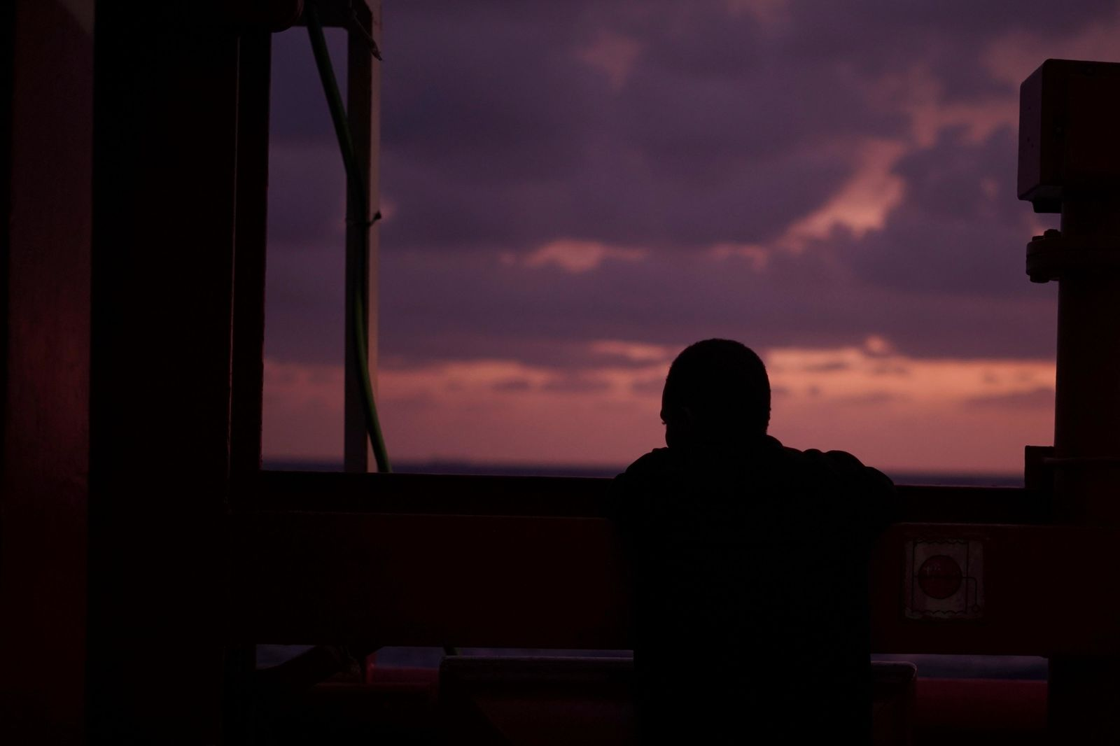 A man looks at the sea from aboard the Ocean Viking in the Mediterranean Sea, Sunday, Sept. 22, 2019. The humanitarian ship carrying 182 people in international waters is sailing back and forth between Italy and Malta as it waits for European governments to allow it in. (AP Photo/Renata Brito)