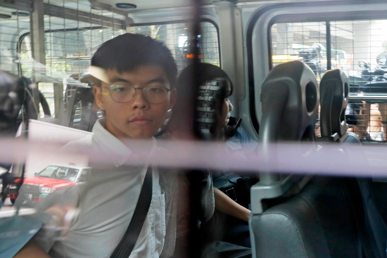 Pro-democracy activists Joshua Wong, left, and Agnes Chow, are escorted in a police van at a district court in Hong Kong, Friday, Aug. 30, 2019. ears to a harder line on this summer's protests. (AP Photo/Kin Cheung)