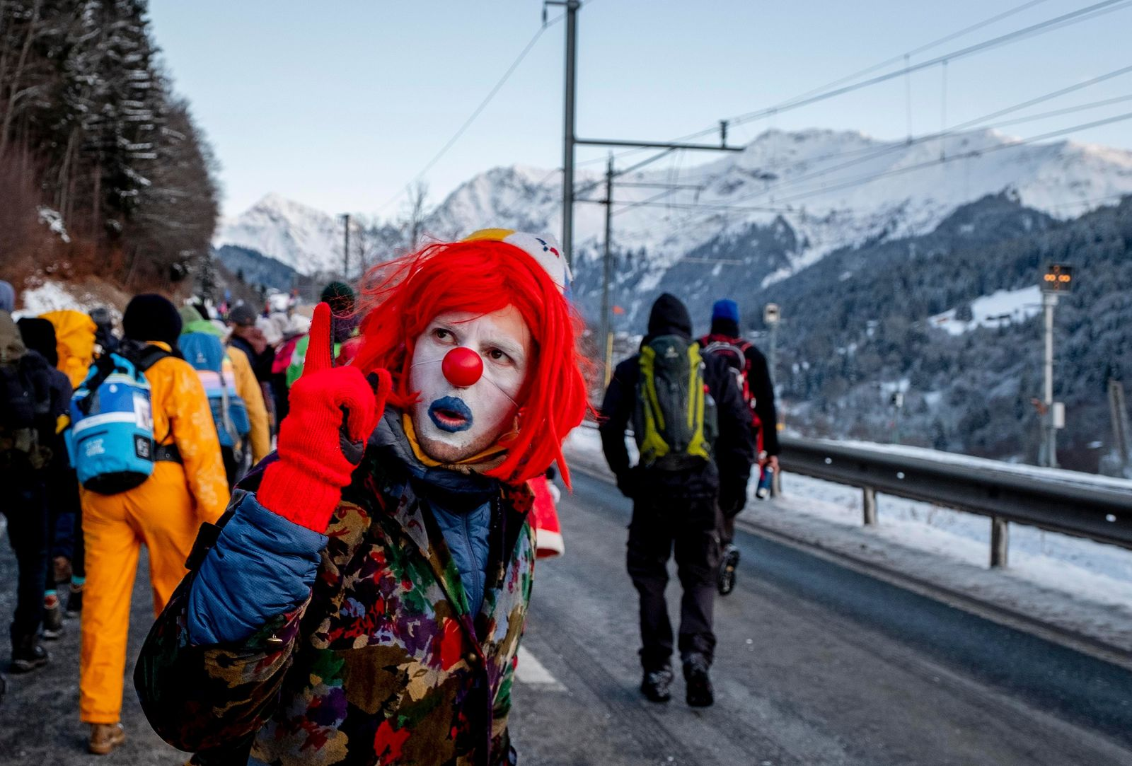 A man dressed as a clown is part of hundreds of climate protesters who are on a three-day  protest march from Landquart (AP Photo/Michael Probst)