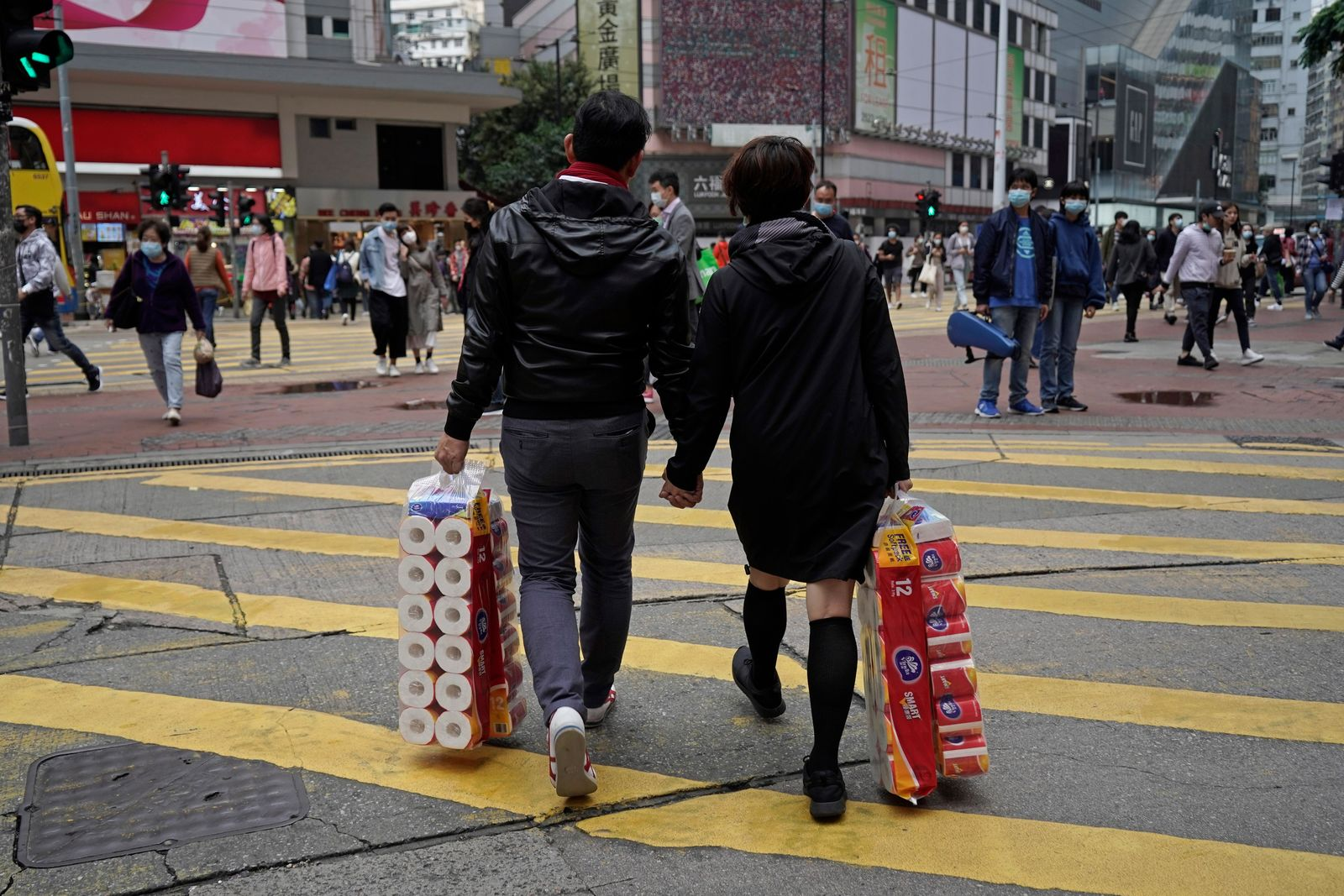 A couple carry a supply of toilet paper at a street on Valentine's Day in Hong Kong, Friday, Feb. 14, 2020. China on Friday reported another sharp rise in the number of people infected with a new virus, as the death toll neared 1,400. (AP Photo/Kin Cheung)