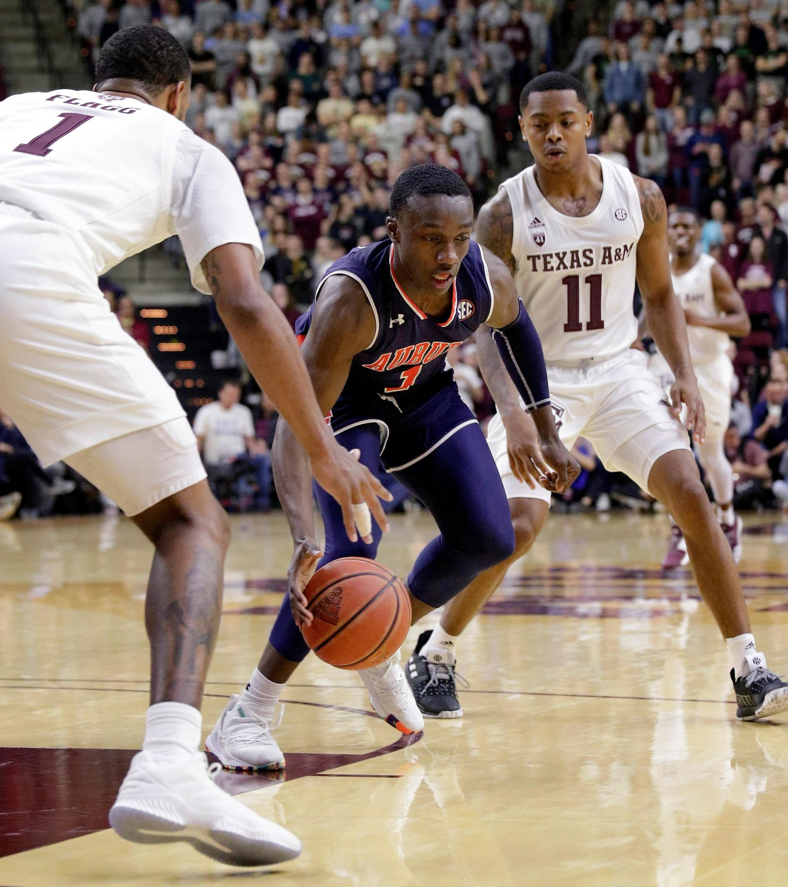 Auburn guard Jared Harper (1) drives between Texas A&M guard Savion Flagg (1) and guard Wendell Mitchell (11) during the second half of an NCAA college basketball game, Wednesday, Jan. 16, 2019, in College Station, Texas. (AP Photo/Michael Wyke)