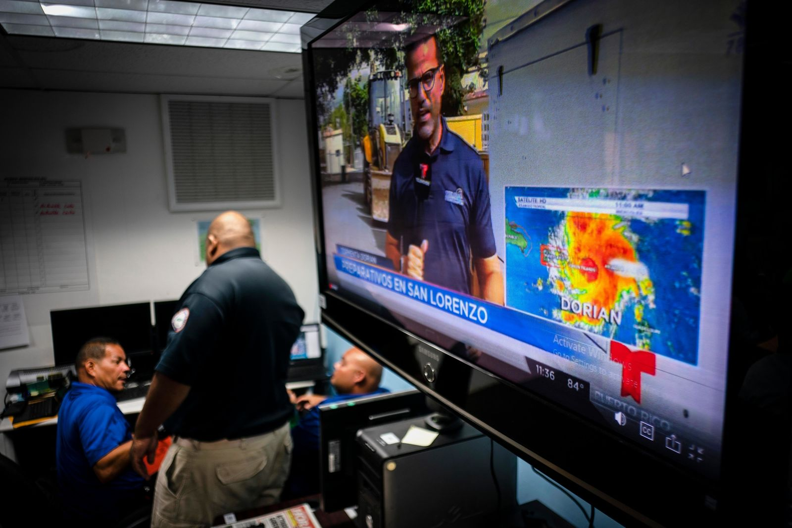 Emergency Center personnel stand next to a tv screen showing a meteorological image of the tropical storm Dorian, as they await its arrival, in Ceiba, Puerto Rico, Wednesday, Aug. 28, 2019. (AP Photo/Ramon Espinosa)