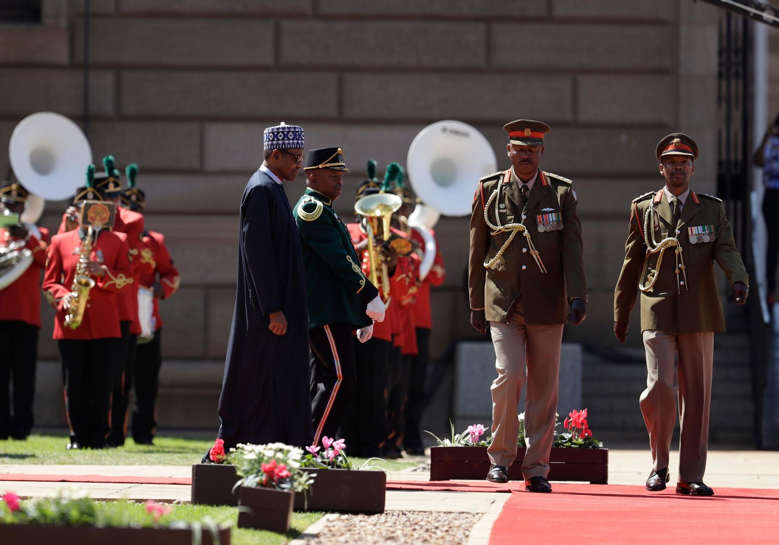 Nigerian President Muhammadu Buhari inspects a guard of honour at a welcoming ceremony in Pretoria, South Africa Thursday, Oct. 3, 2019. (AP Photo/Themba Hadebe)