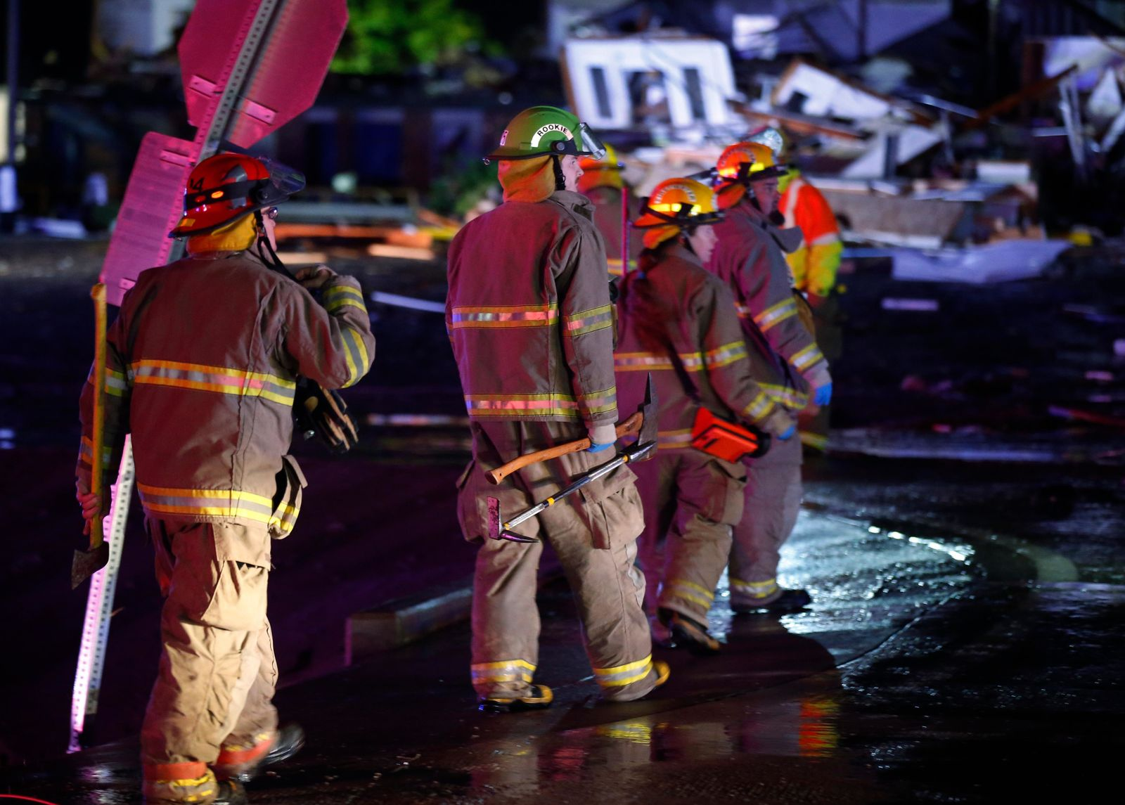 Firefighters walk to an area of debris from a hotel and a mobile home park in El Reno, Okla., Sunday, May 26, 2019, following a likely tornado touchdown late Saturday night. (AP Photo/Sue Ogrocki)