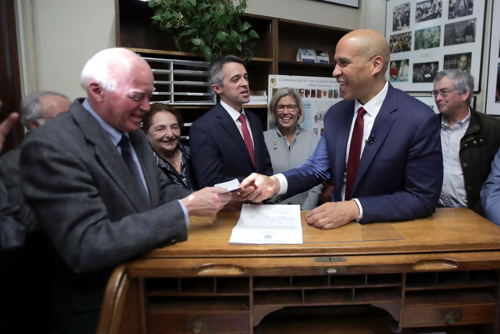 Democratic presidential candidate Sen. Cory Booker, D-N.J., pays the filing fee to have his name listed on the New Hampshire primary ballot, Friday, Nov. 15, 2019, in Concord, N.H. At left is New Hampshire Secretary of State Bill Gardner. (AP Photo/Charles Krupa)