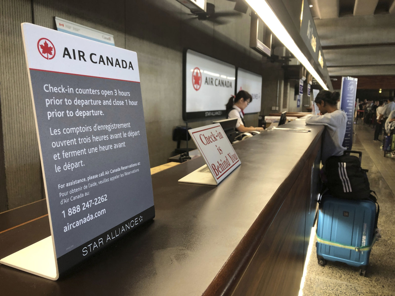 Passengers from an Australia-bound Air Canada flight diverted to Honolulu Thursday, July 11, 2019, after about 35 people were injured during turbulence, stand in line at the Air Canada counter at Daniel K. Inouye International Airport to rebook flights. (AP Photo/Caleb Jones)