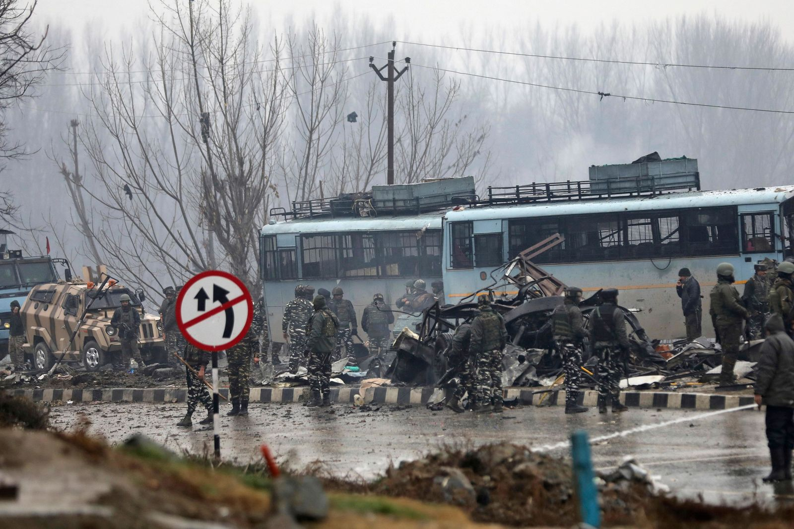Indian paramilitary soldiers stand by the wreckage of a bus after an explosion in Pampore, Indian-controlled Kashmir, Thursday, Feb. 14, 2019.{ } (AP Photo/Umer Asif)
