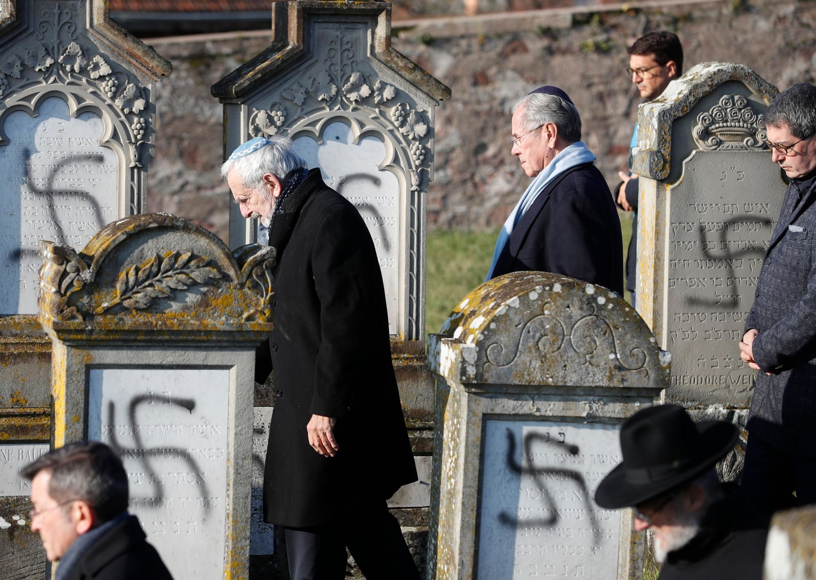 Members of the Jewish community walk amid vandalized tombs in the Jewish cemetery of Westhoffen, west of the city of Strasbourg, eastern France, Wednesday, Dec. 4, 2019.{ } (AP Photo/Jean-Francois Badias)