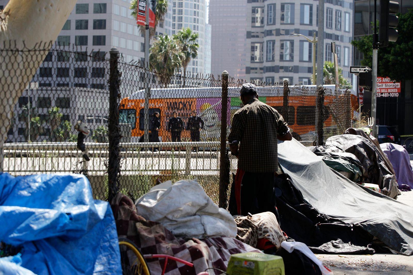 A newly displaced homeless camp is seen while Los Angeles Police officers guard a Harbor Freeway ramp during the visit of President Donald Trump in Los Angeles, Tuesday, Sept. 17, 2019. ess but offering no specifics beyond the mention of creating a task force. (AP Photo/Damian Dovarganes)
