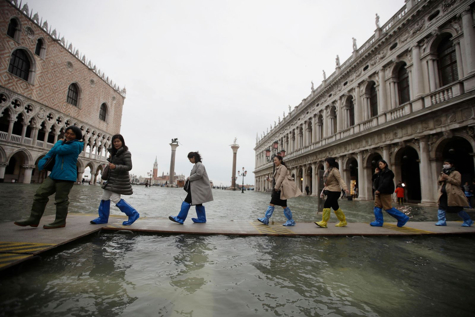 People use trestle bridges to walk in a flooded St. Mark's Square at Venice, Friday, Nov. 15, 2019. (AP Photo/Luca Bruno)