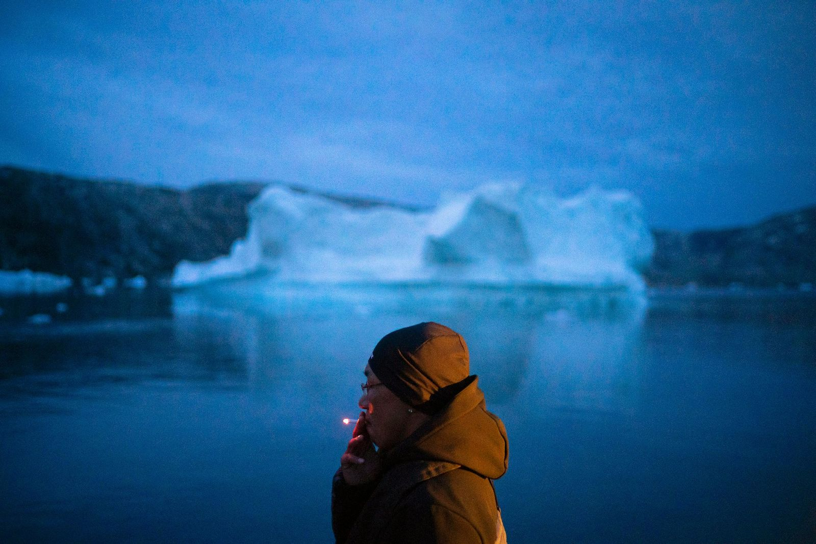A local man smokes a cigarette as he rides on a boat past icebergs in eastern Greenland, late Friday, Aug. 15, 2019.{ } (AP Photo/Felipe Dana)