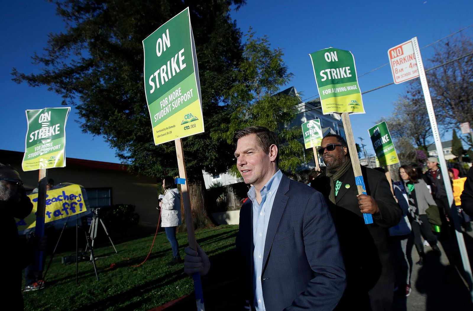 Rep. Eric Swalwell, D-Calif., center, marches with Oakland Education Association President Keith Brown, center right, along with teachers and supporters outside of Manzanita Community School in Oakland, Calif., Thursday, Feb. 21, 2019. (AP Photo/Jeff Chiu)