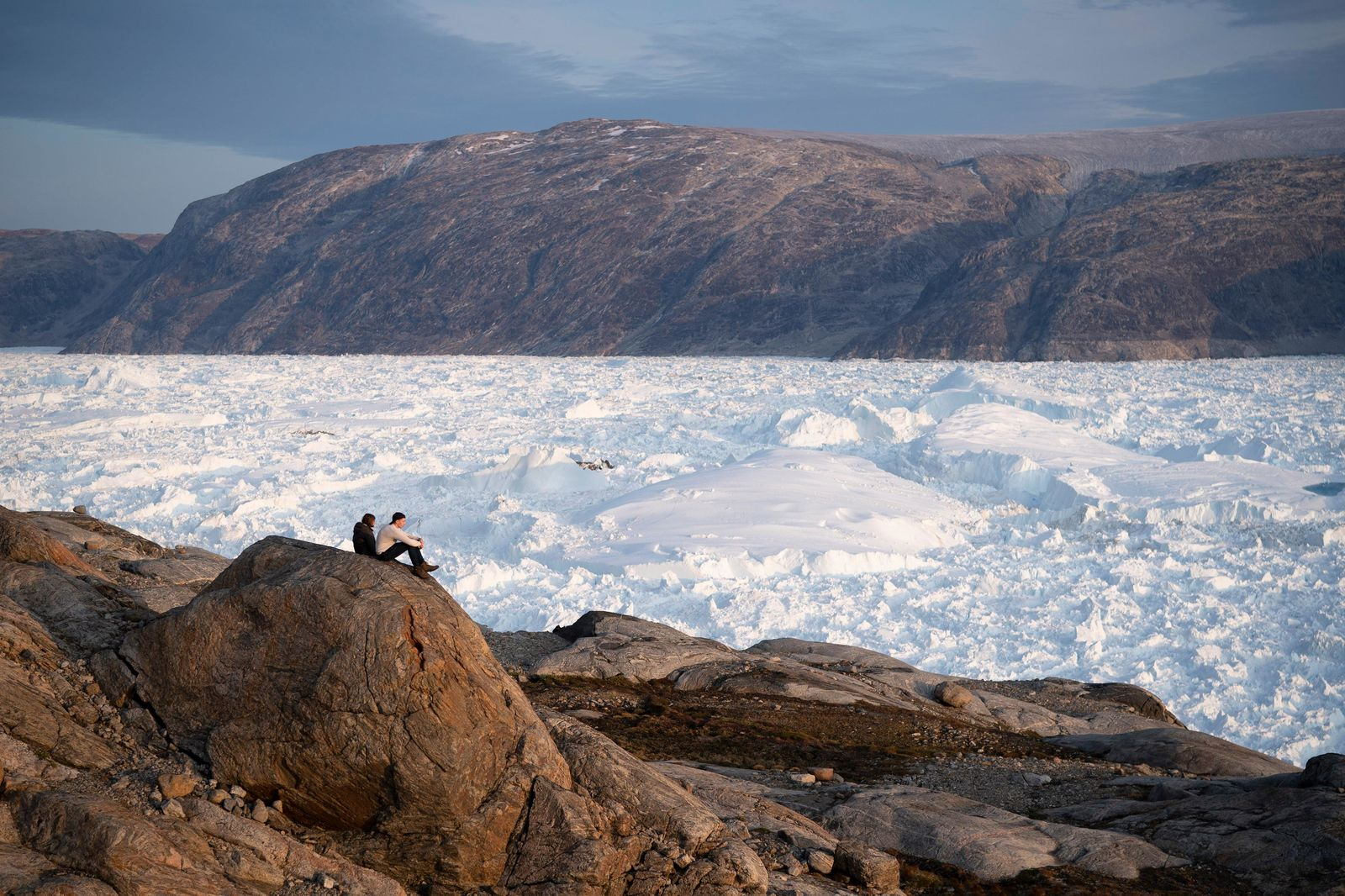 In this Aug. 16, 2019, photo, NYU student researchers sit on top of a rock overlooking the Helheim glacier in Greenland. Summer 2019 is hitting the island hard with record-shattering heat and extreme melt.{ } (AP Photo/Felipe Dana)
