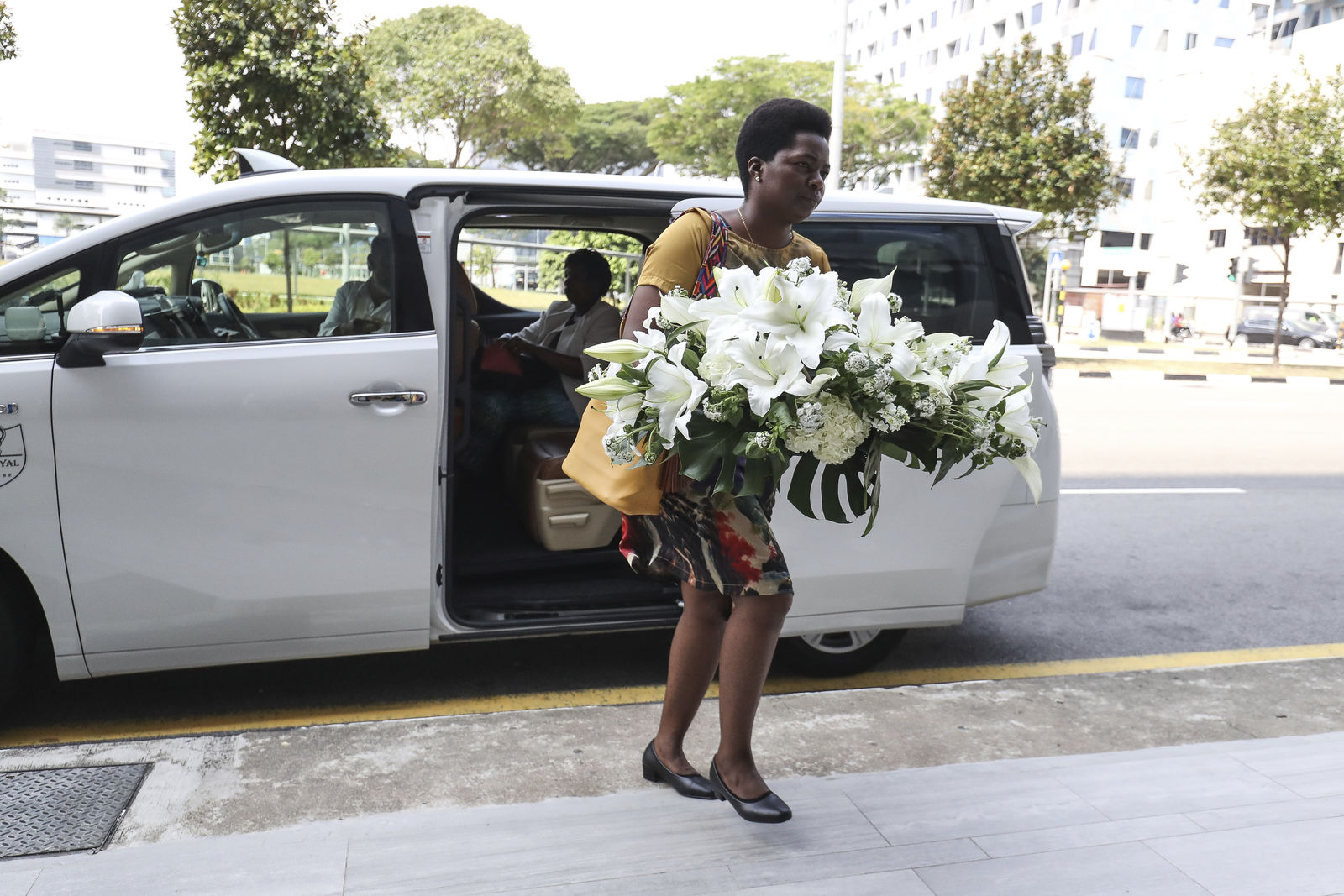 A visitor arrives with a wreath at the Singapore Casket funeral parlor building where the body of the late former president of Zimbabwe is being held on Saturday, Sept. 7, 2019, in Singapore. Robert Mugabe, the former leader of Zimbabwe forced to resign in 2017 after a 37-year rule whose early promise was eroded by economic turmoil, disputed elections and human rights violations, has died in Singapore. He was 95. (AP Photo/Danial Hakim)