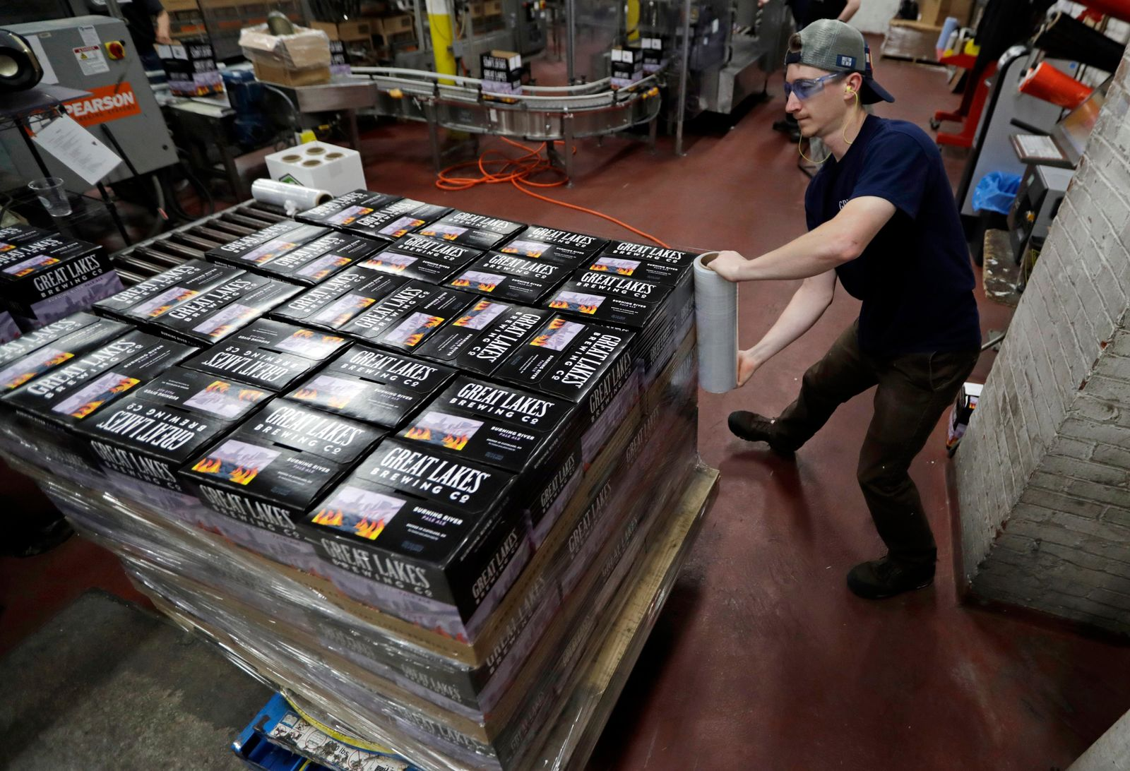 "A worker shrink wraps cases of Burning River beer at The Great Lakes Brewing Company, Monday, June 17, 2019, in Cleveland. The ""burning river"" in the beer's name is inspired by the Cuyahoga River's most famous fire. (AP Photo/Tony Dejak)"