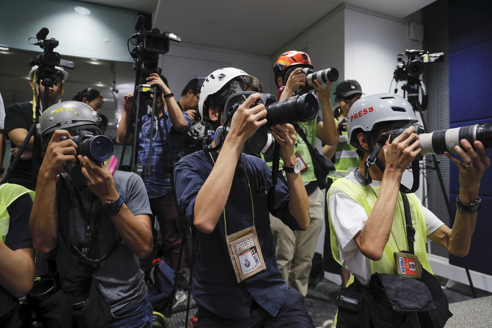 In a sign of protest against the police using force against the media, press photographers wear protective gear during a police media conference in Hong Kong, on Monday, Sept. 9, 2019.{ } (AP Photo/Kin Cheung)