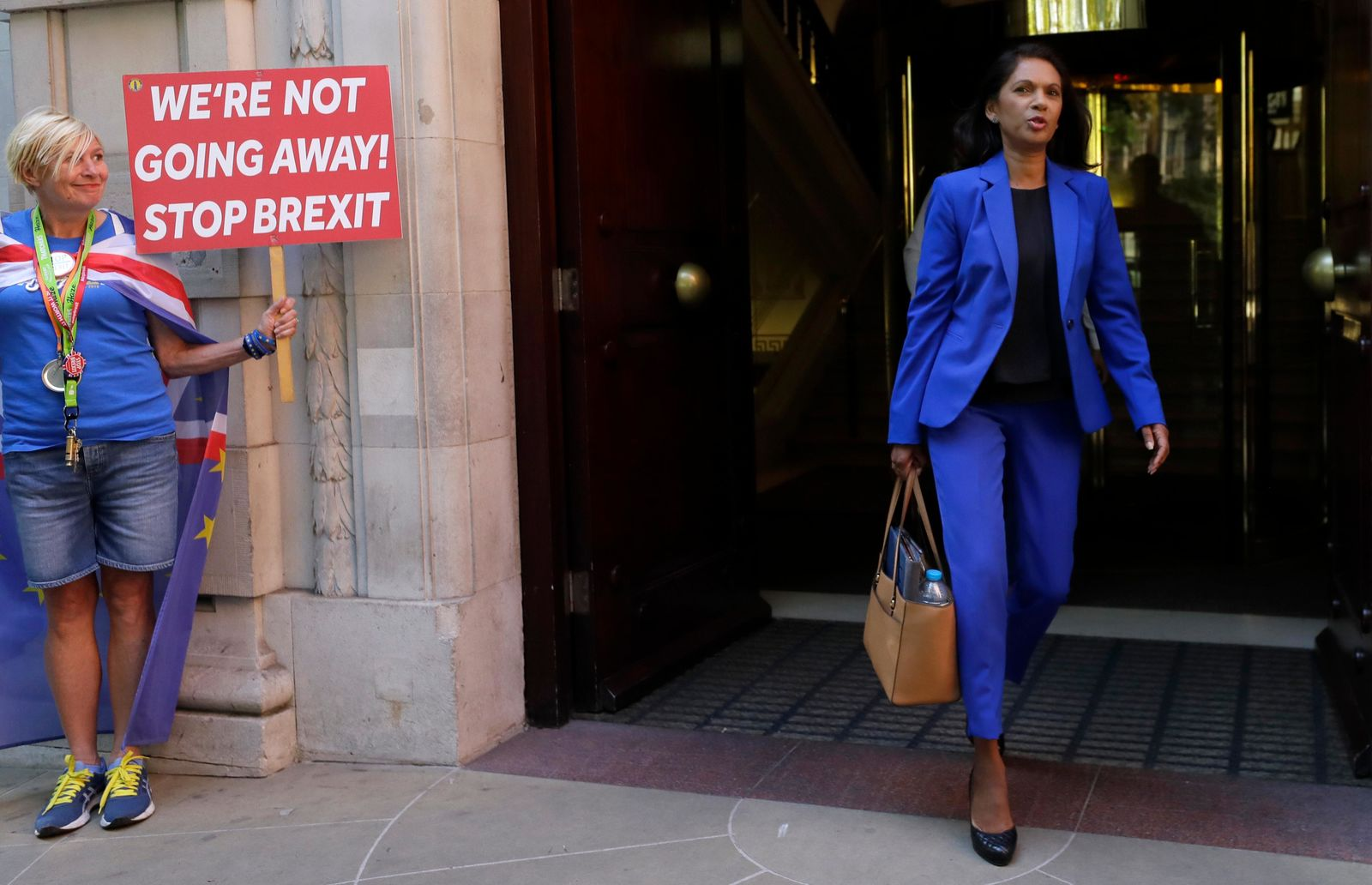 Campaigner Gina Miller, right, leaves Millbank studios in London, Thursday, Aug. 29, 2019.{ } (AP Photo/Kirsty Wigglesworth)