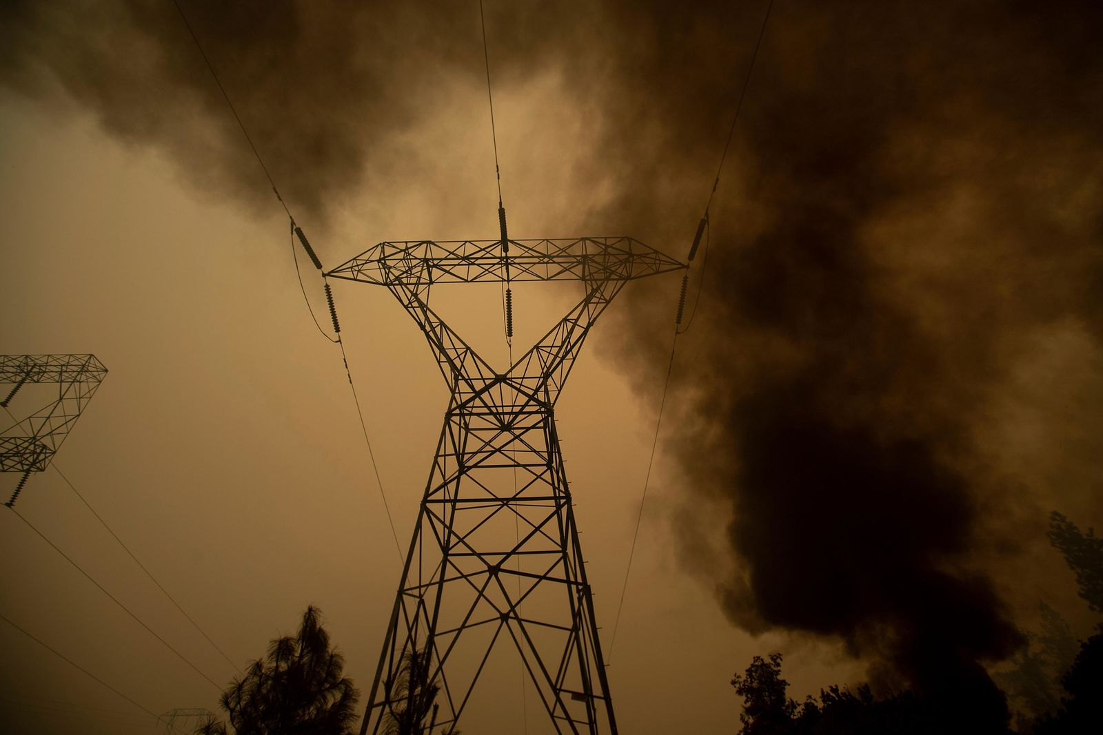 FILE - In this Nov. 9, 2018, file photo, smoke billows around power transmission lines as the Camp Fire burns in Big Bend, Calif. Experts say it's hard to know whether keeping millions of Californians in the dark prevented a catastrophic wildfire.{ } { }(AP Photo/Noah Berger, File)