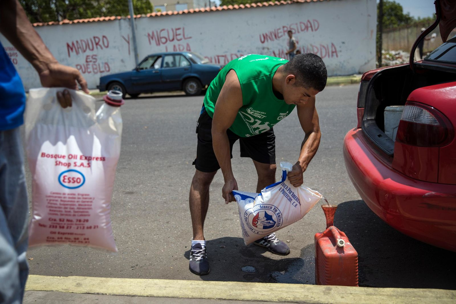 Jesus Gonzales fills a container with bagged gasoline he bought at extra cost at a fuel station, in order to not wait in the longer line in Cabimas, Venezuela, Saturday, May 18, 2019.(AP Photo/Rodrigo Abd)