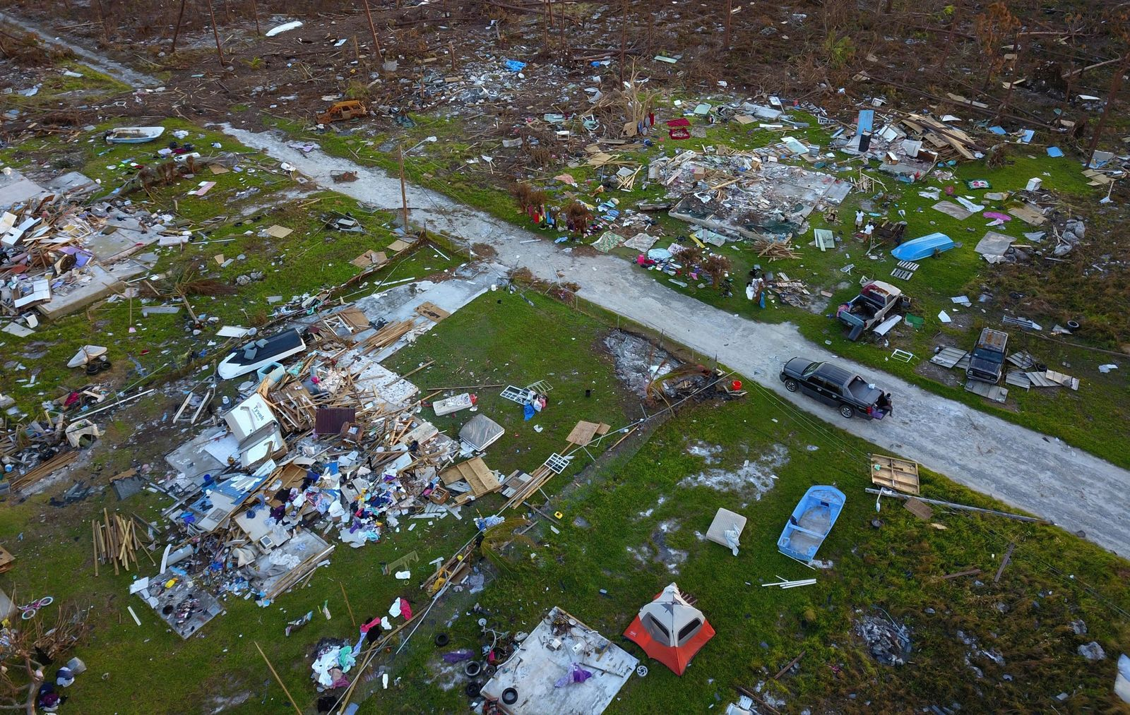 A road cuts through the rubble of homes that belong to the same family, destroyed by Hurricane Dorian in Rocky Creek East End, Grand Bahama, Bahamas, Sunday, Sept. 8, 2019. (AP Photo/Ramon Espinosa)