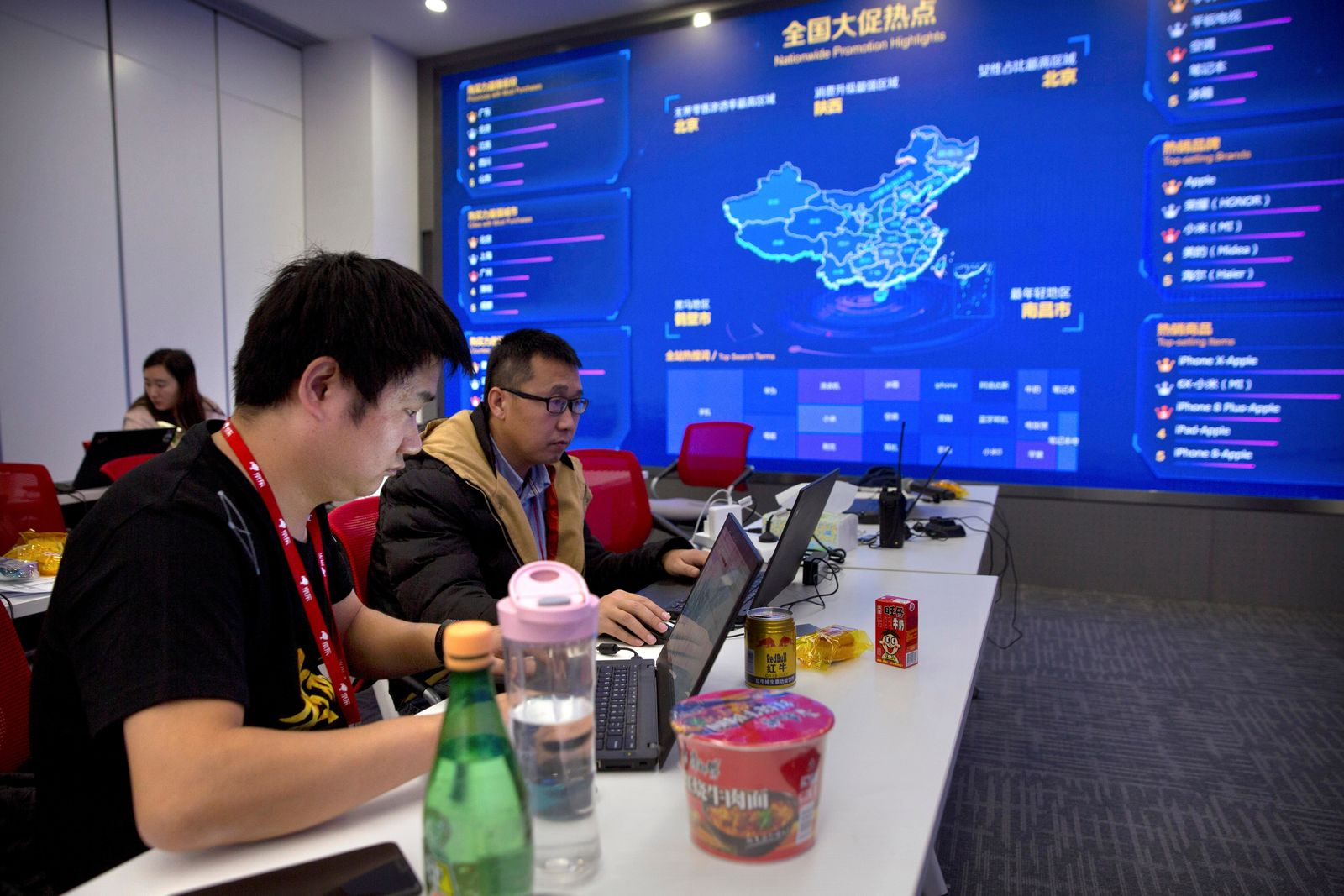 FILE - In this Nov. 11, 2018, file photo, workers use their laptops near a display showing sales data at the command center at the headquarters of an e-commerce retailer in Beijing. Remarks by the head of Chinese online business giant Alibaba that young people should work 12-hour days, six days a week if they want financial success have prompted a public debate over work-life balance in the country. (AP Photo/Mark Schiefelbein, File)