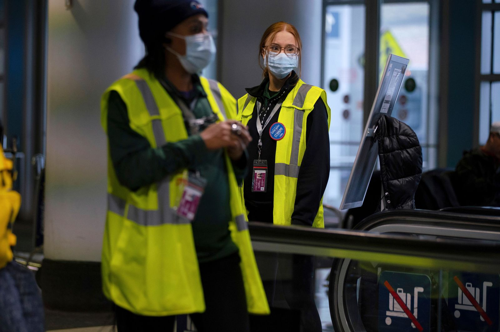 Airport employees wear face masks in Terminal 5 at O'Hare International Airport, Friday, Jan. 24, 2020 in Chicago. A Chicago woman has become the second U.S. patient diagnosed with the dangerous new virus from China, health officials announced Friday. (E. Jason Wambsgans/Chicago Tribune via AP)