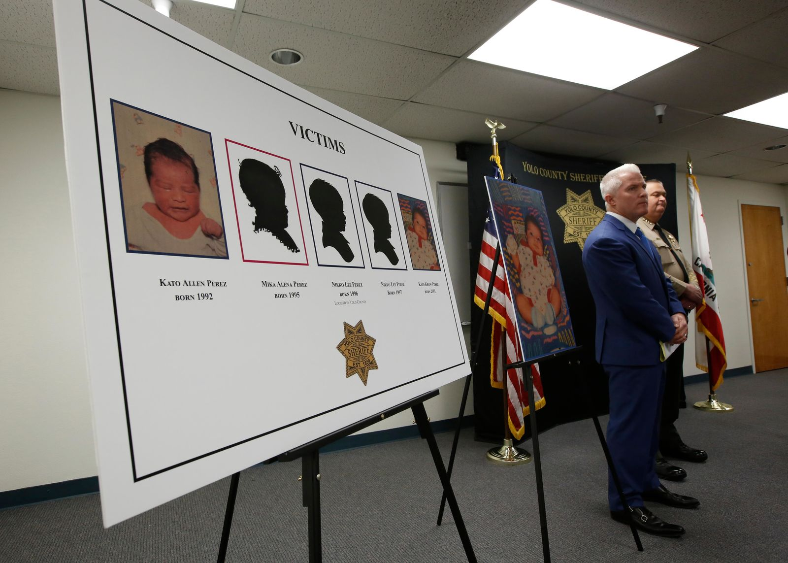 A poster of five infants believed to be killed by their father is displayed during a news conference, attended by Yolo County District Attorney Jeff Reisig, left, and Sheriff Tom Lopez, right, in Woodland, Calif., Monday, Jan. 27, 2020. Paul Perez, 57, has been arrested in the decades-old killings of five of his infant children, a case the sheriff said had haunted his agency for years, the Yolo County Sheriff's Office said Monday, Jan. 27, 2020. (AP Photo/Rich Pedroncelli)