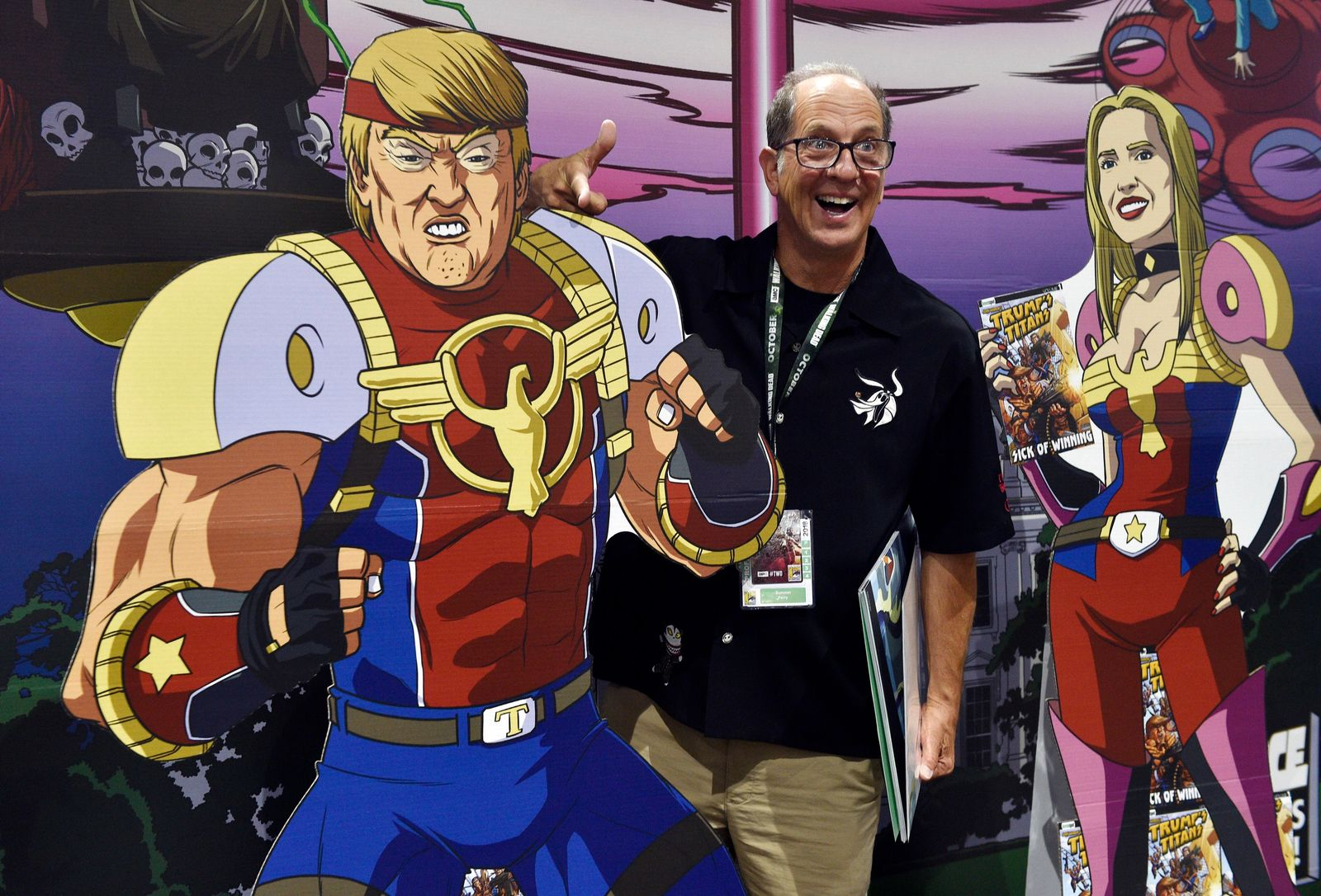 "Paul Nestor, of San Diego, poses next to cut-out figures of President Donald Trump and his daughter Ivanka at a booth for the satirical comic book series ""Trump's Titans"" during Preview Night of the 2018 Comic-Con International at the San Diego Convention Center, Wednesday, July 18, 2018, in San Diego. (Photo by Chris Pizzello/Invision/AP)"