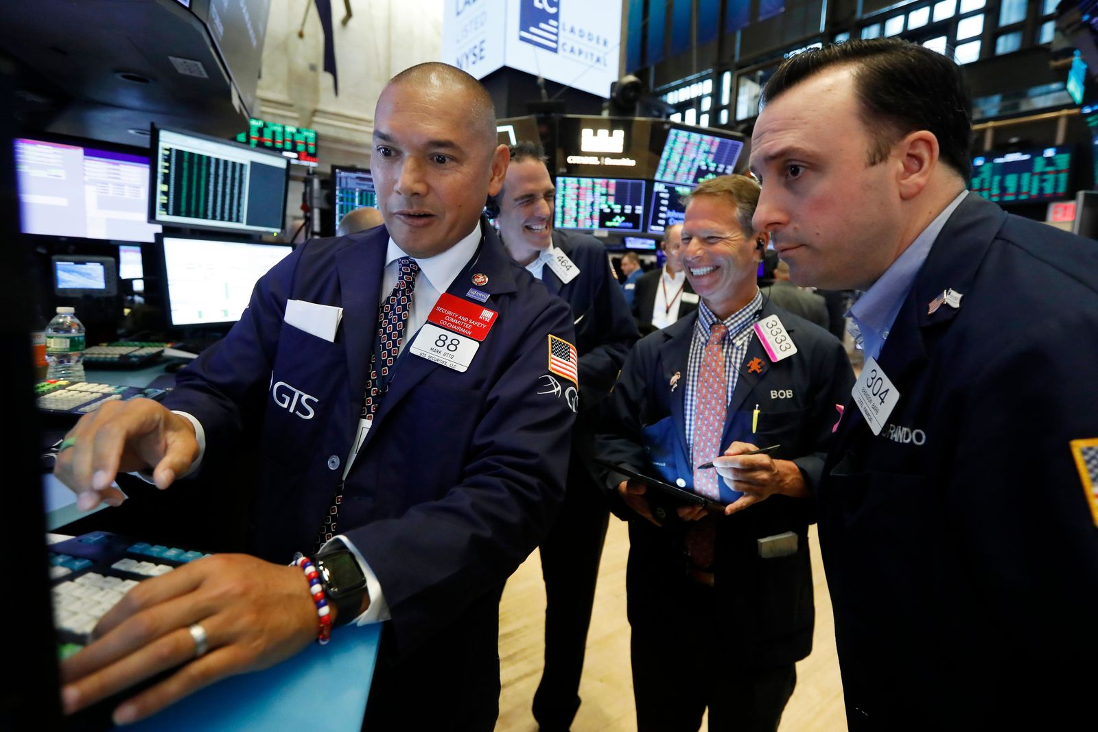 Specialist Mark Otto, left, works with traders at his post on the floor of the New York Stock Exchange, Friday, Aug. 16, 2019. Stocks are opening broadly higher at the end of a turbulent week. (AP Photo/Richard Drew)