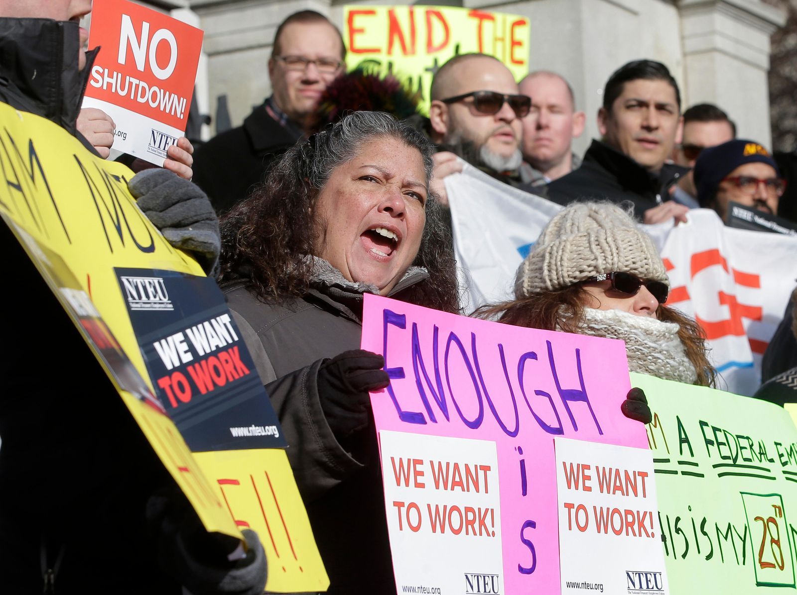 Internal Revenue Service employee Mary Maldonado, of Dracut, Mass., center, displays a placard during a rally by federal employees and supporters, Thursday, Jan. 17, 2019, in front of the Statehouse, in Boston, held to call for an end of the partial shutdown of the federal government. (AP Photo/Steven Senne)
