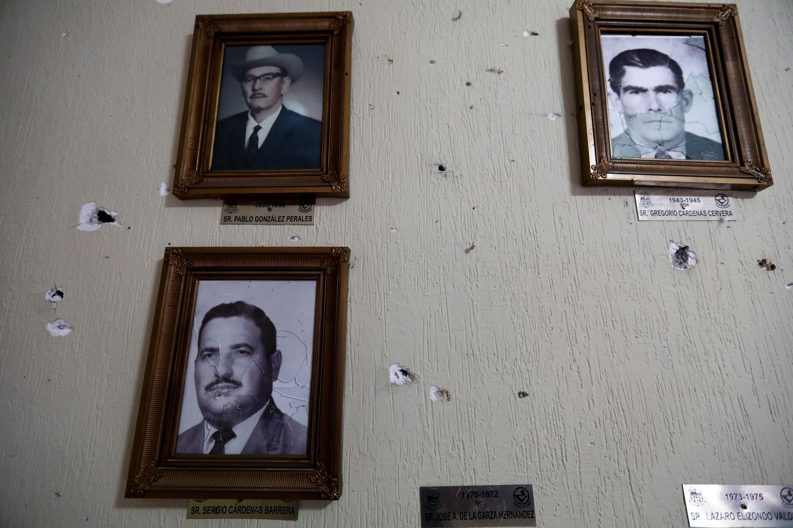 Portraits of former mayors of Villa Union hang on a wall riddled with bullet holes after a gunbattle, inside City Hall, in Villa Union, Mexico, Monday, Dec. 2, 2019. The small town near the U.S.-Mexico border began cleaning up Monday even as fear persisted after 22 people were killed in a weekend gunbattle between a heavily armed drug cartel assault group and security forces. (AP Photo/Eduardo Verdugo)