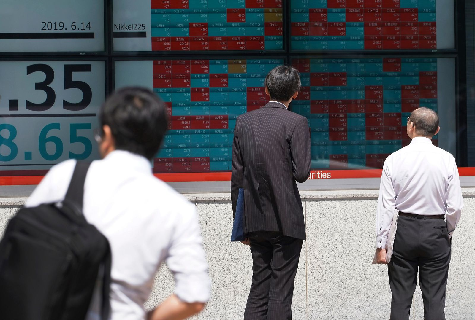 Pedestrians look at an electronic stock board showing Japan's Nikkei 225 index at a securities firm in Tokyo Friday, June 14, 2019. (AP Photo/Eugene Hoshiko)