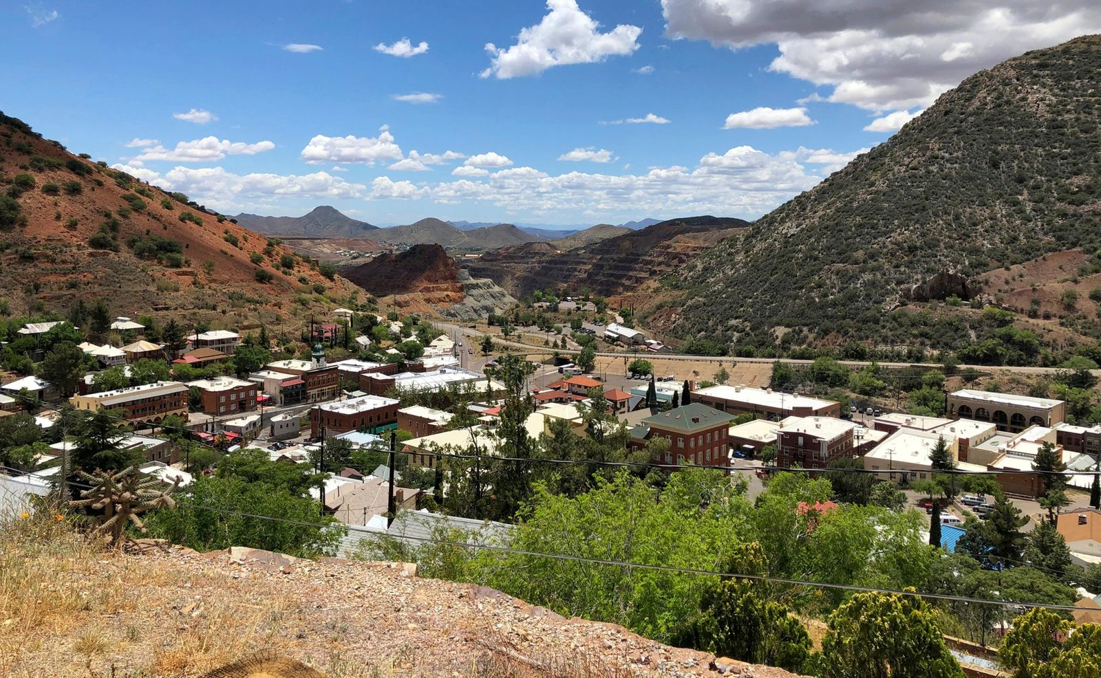 "This May 23, 2019 photo shows modern-day Bisbee, Ariz., with itslarge open-pit copper mine in the background, the subject of ""Bisbee '17,"" a story of how some 1,200 miners, most of them immigrants, were pulled violently from their homes in Bisbee by a private police force and put on cattle cars for deportation to a desolate area of New Mexico in 1917. (AP Photo/Anita Snow)"