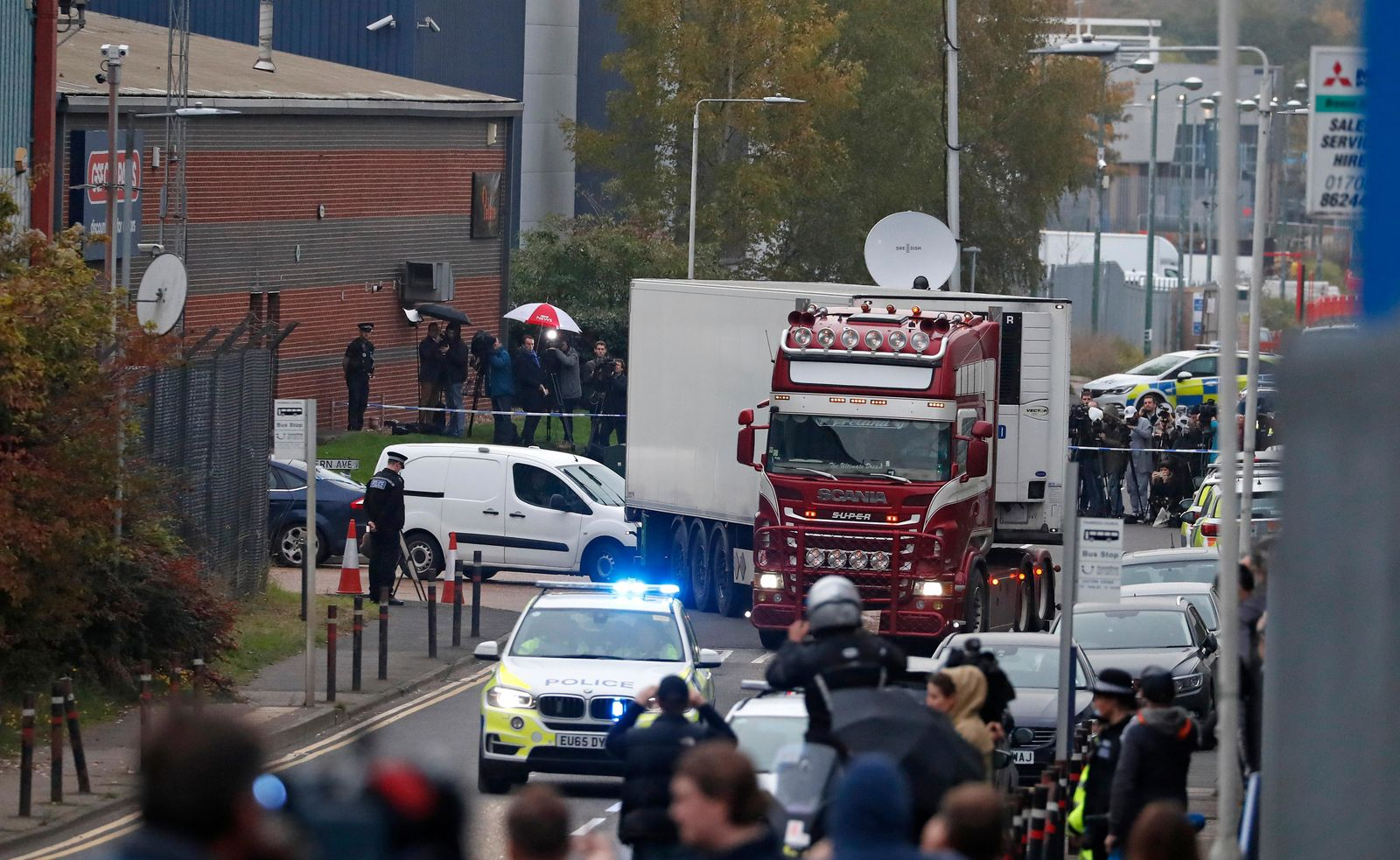 Police escort the truck, that was found to contain a large number of dead bodies, as they move it from an industrial estate in Thurrock, south England, Wednesday Oct. 23, 2019.{ } (AP Photo/Alastair Grant)