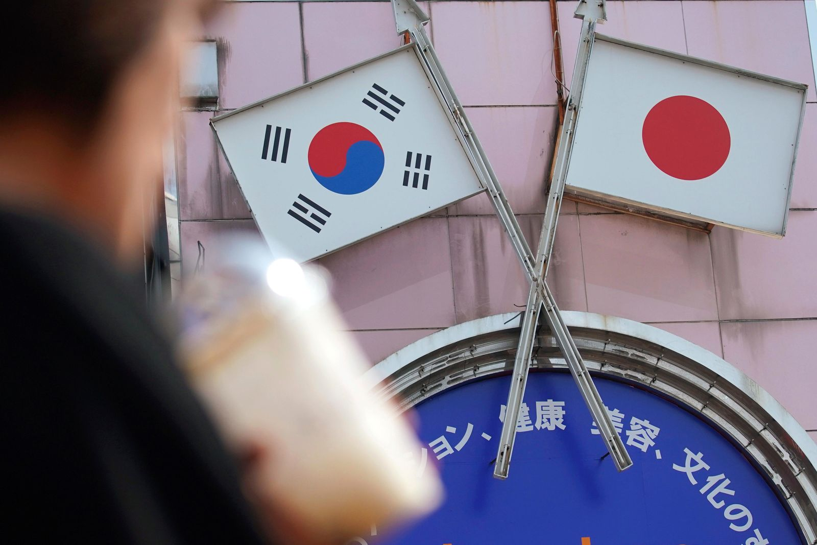 FILE - In this Aug. 2, 2019, file photo, a woman walks past an advertisement featuring Japanese and South Korean flags at a shop in Shin Okubo area in Tokyo. (AP Photo/Eugene Hoshiko, File)