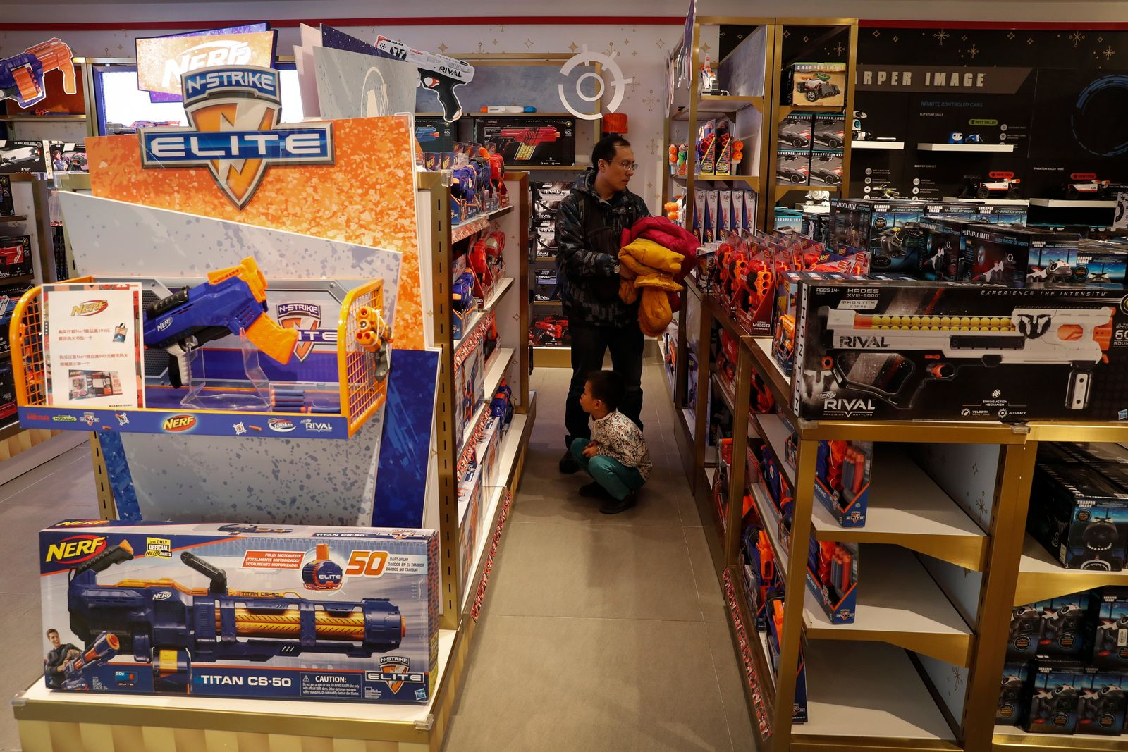 In this Saturday, Dec. 7, 2019, photo, a man and a child look at toy guns on display for sale at the American toy store FAO Schwarz at the capital city's popular shopping mall in Beijing. (AP Photo/Andy Wong)