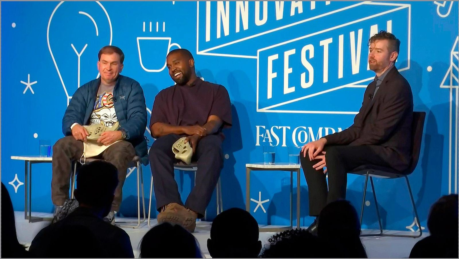 This image taken from video shows Kanye West, right, with Steven Smith, lead designer at Yeezy as Fast Company senior writer Mark Wilson, right, looks on during a discussion on fashion and design at the Fast Company Innovation Festival in New York on Thursday, Nov. 7, 2019. (AP Photo/David Martin)
