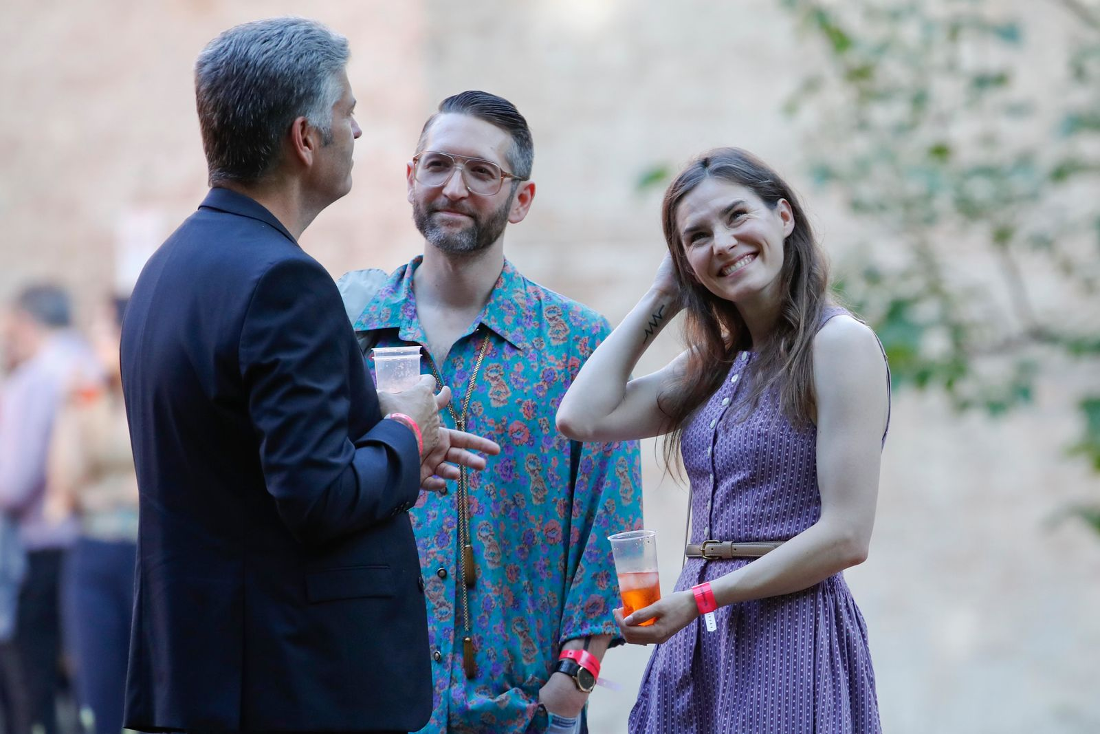 Amanda Knox, right, and her boyfriend Christopher Robinson, center, talk with a guest as they attend a cocktail for the opening of the Innocence Project conference, in Modena, Italy, Thursday, June 13, 2019. (AP Photo/Antonio Calanni)(AP Photo/Antonio calanni)