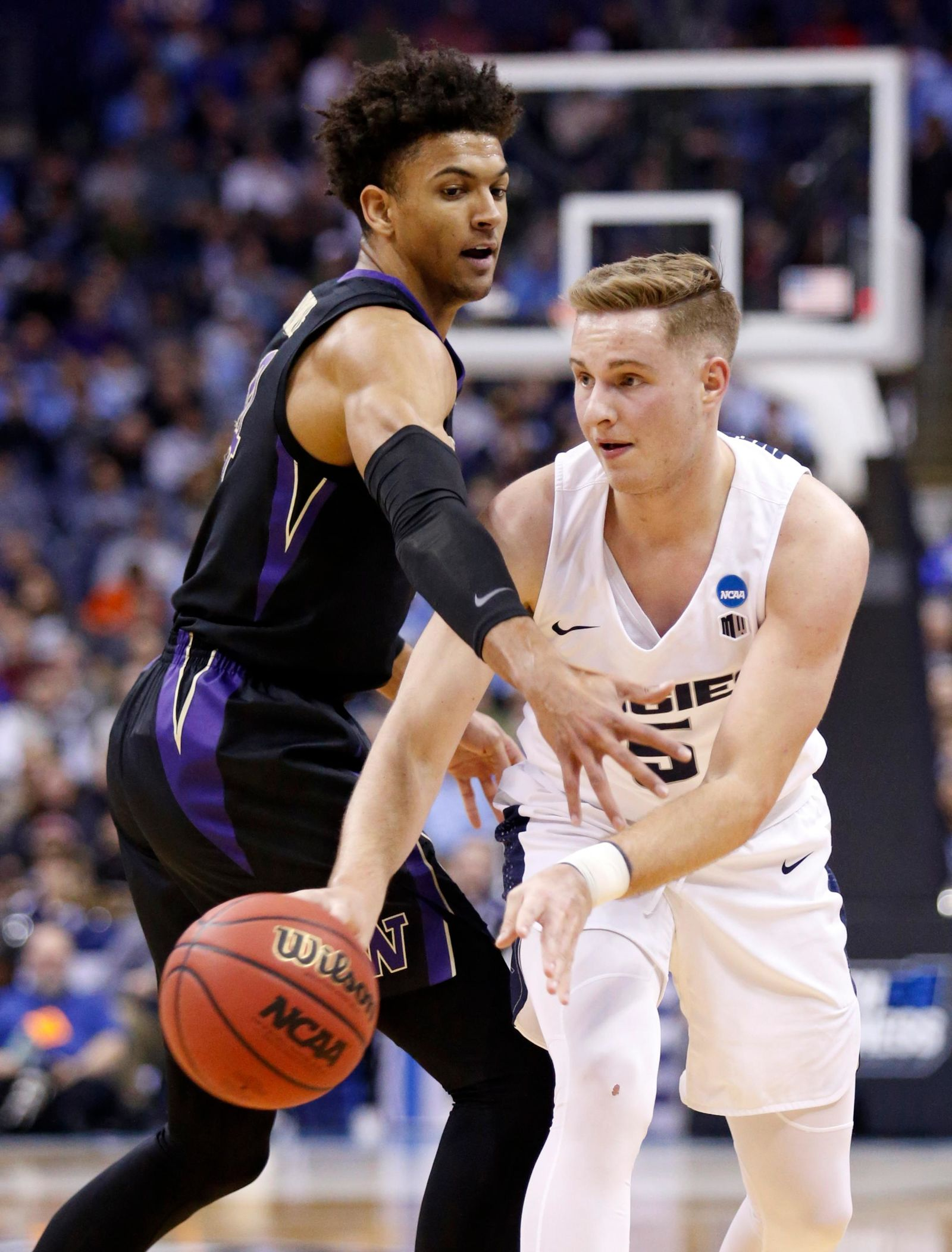 Utah State's Sam Merrill, right, passes against Washington's Matisse Thybulle in the first half of a first-round game in the NCAA men's college basketball tournament in Columbus, Ohio, Friday, March 22, 2019. (AP Photo/Paul Vernon)