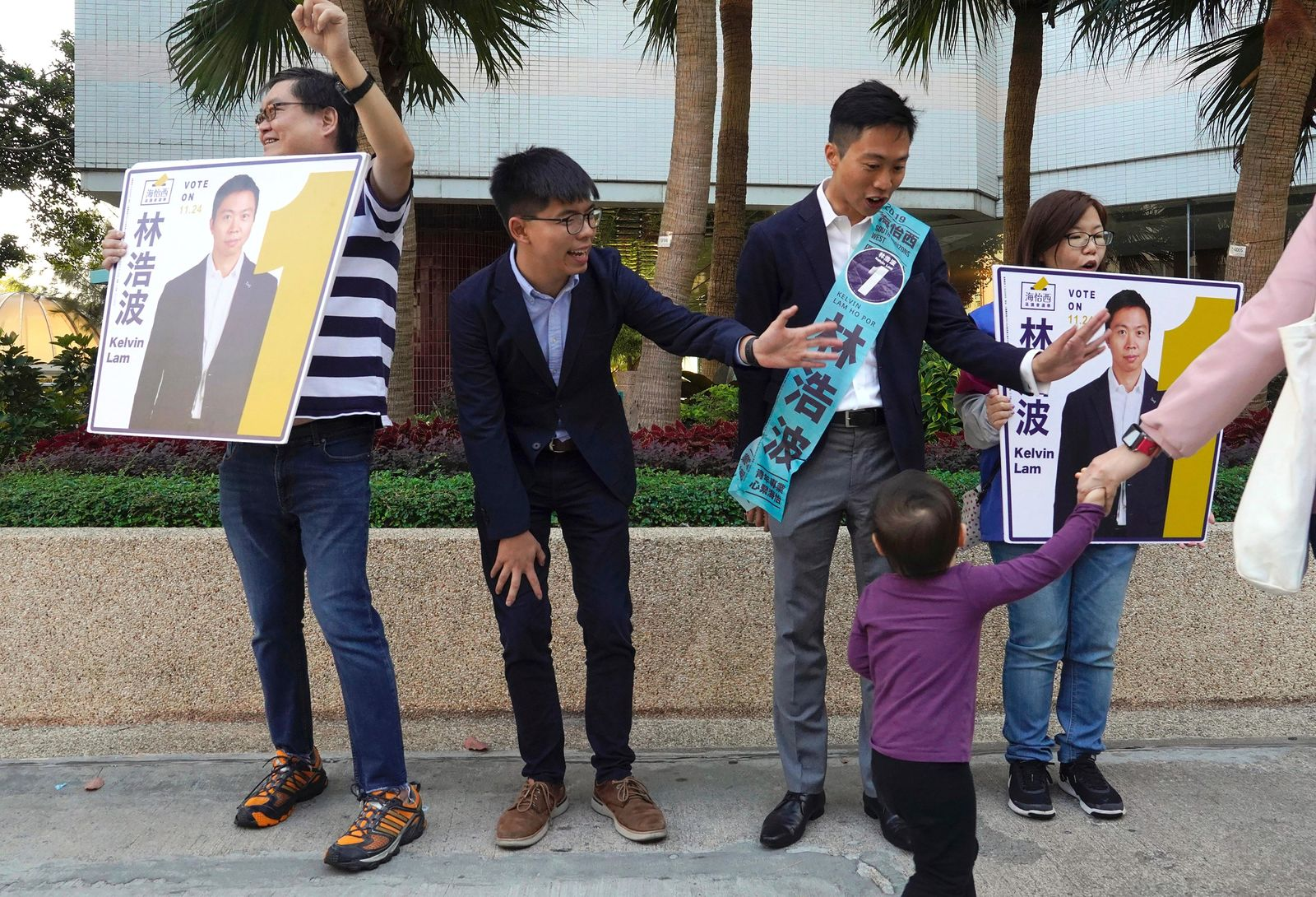 "Pro-democracy activist Joshua Wong, second from left, campaigns with local election candidate Kelvin Lam, second from right, in Hong Kong, Saturday, Nov. 23, 2019. Chanting ""No more tear gas,"" dozens of Hong Kong families with young children are marching to oppose the government's handling of protests on the eve of keenly contested local elections. (AP Photo/Vincent Yu)"