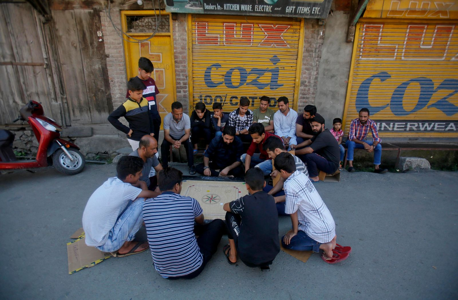 Kashmiri men play a board game at a closed market during security restrictions in Srinagar, Indian controlled Kashmir, Tuesday, Aug. 20, 2019. The president of Pakistani-administered Kashmir welcomed efforts by U.S. President Donald Trump to lower tensions between Pakistan and India over the disputed Himalayan region on Tuesday and warned of a deepening humanitarian crisis and food shortages in the Indian-held portion. (AP Photo/Mukhtar Khan)
