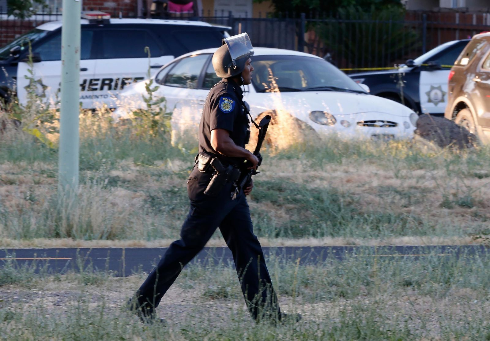 A Sacramento Police officer responds to the shooting of a fellow officer in Sacramento, Calif., Wednesday, June 19, 2019. (AP Photo/Rich Pedroncelli)