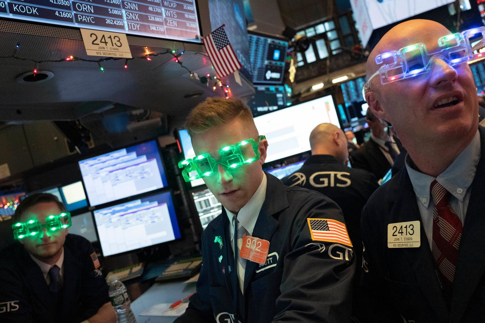 Stock traders wear New Year's 2020 party glasses at the New York Stock Exchange, Tuesday, Dec. 31, 2019. Stocks slipped globally in quiet New Year's Eve trading Tuesday with many markets closed. Wall Street could close 2019 with back-to-back daily losses in a year that the U.S. posted the largest market gains since 2013. (AP Photo/Mark Lennihan)