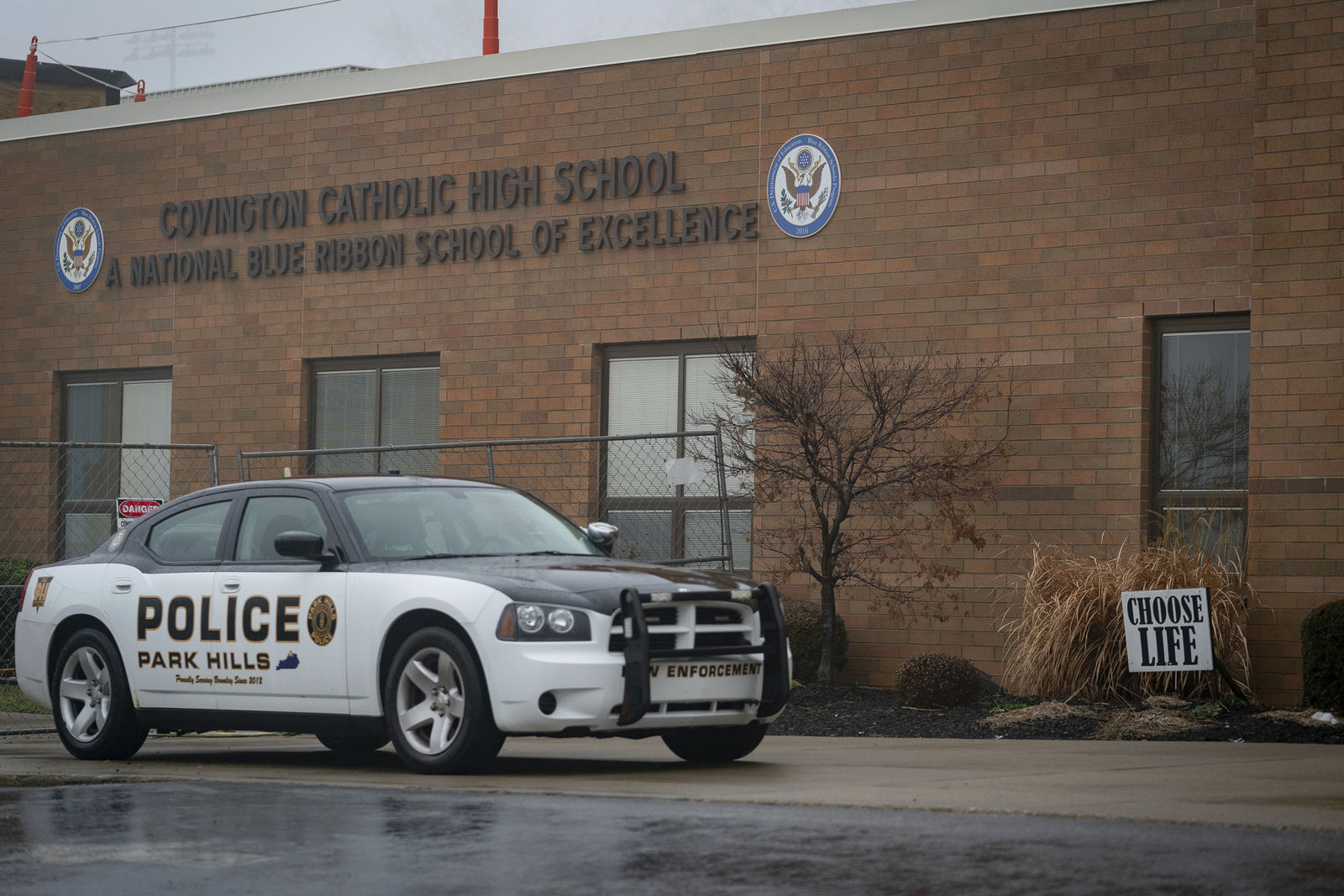 A police car sits in front of Covington Catholic High School in Park Hills, Ky., Saturday, Jan 19, 2019. (AP Photo/Bryan Woolston)