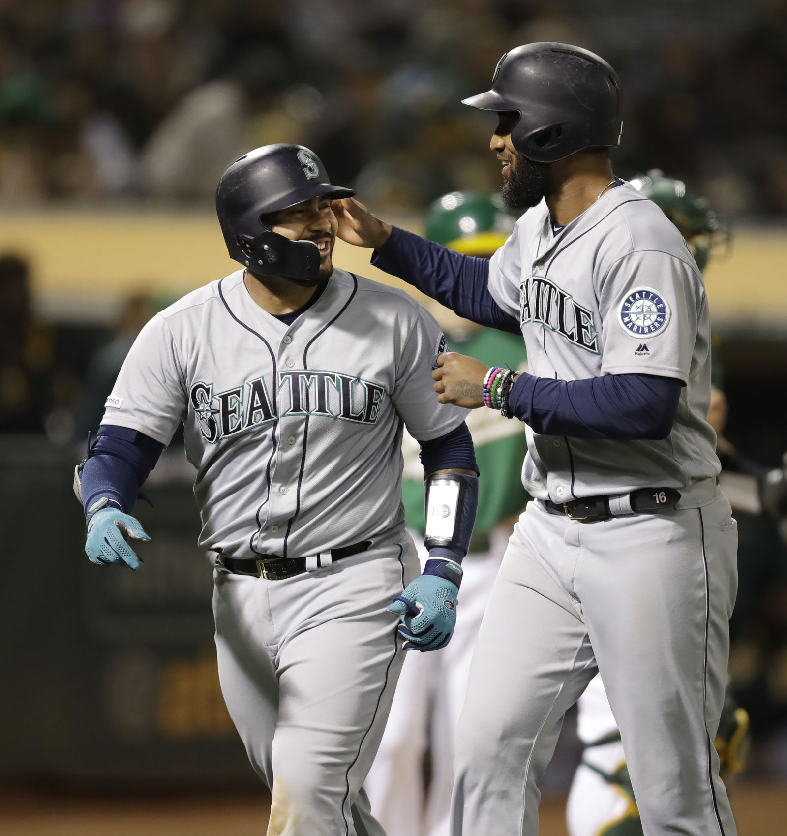 Seattle Mariners' Omar Narvaez, left, celebrates with Domingo Santana after hitting a two-run home run off Oakland Athletics' Wei-Chung Wang during the seventh inning of a baseball game Friday, June 14, 2019, in Oakland, Calif. (AP Photo/Ben Margot)